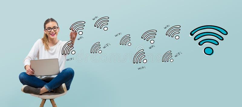 WiFi tema med den unga kvinnan arkivfoto