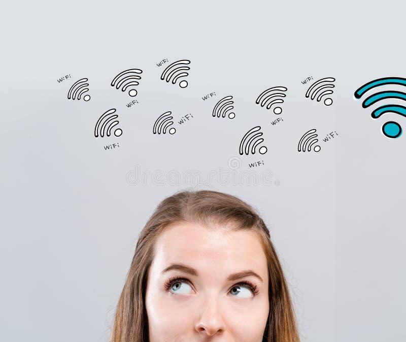 WiFi tema med den unga kvinnan royaltyfri bild