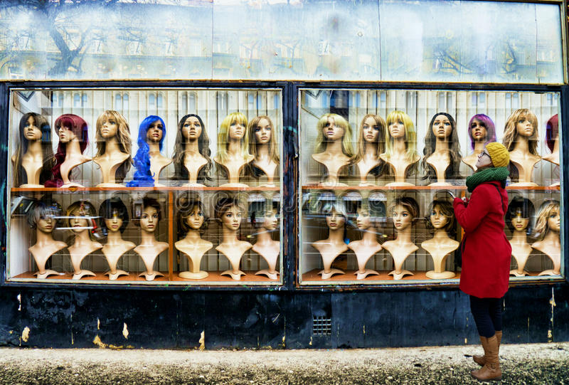 The wig shop. Street photo style photo of a young woman looking at a weathered wig shop with lots of mannequin heads on display wearing different artificial hair stock images