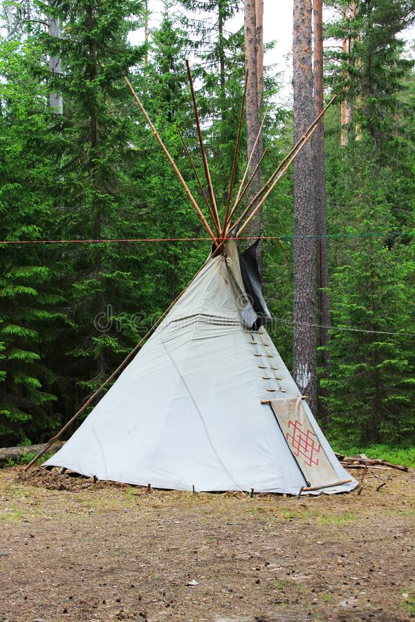 wigwam or teepee standing in summer coniferous forest. royalty free stock photography