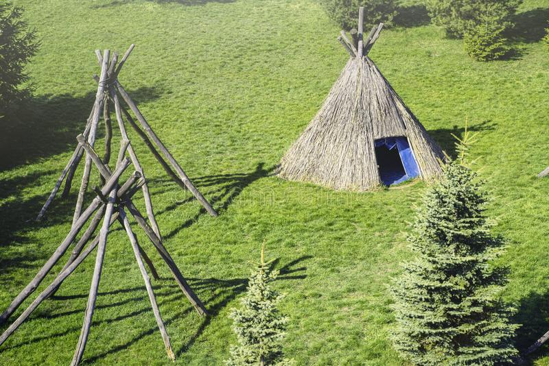 Wigwam type thatch huts in native american camp site.Wigwam type thatch huts .Straw wigwam on a glade on a sunny spring day. Wigwam type thatch huts .Straw stock image