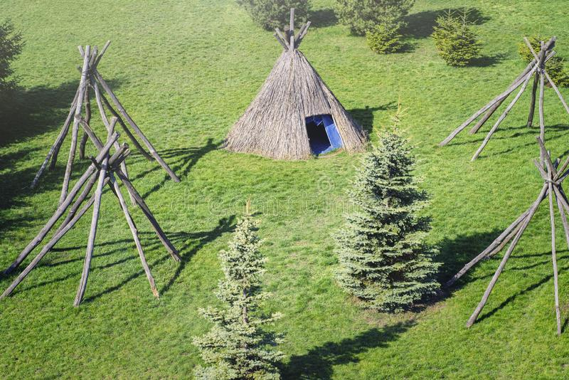 Wigwam type thatch huts in native american camp site.Wigwam type thatch huts .Straw wigwam on a glade on a sunny spring day. Wigwam type thatch huts .Straw royalty free stock image