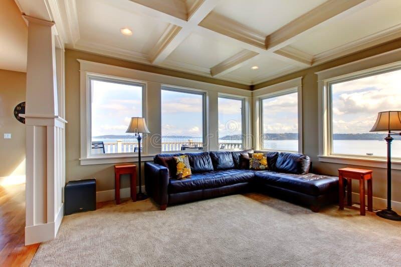 Wih del salone molti grandi finestre e sofà blu. immagine stock