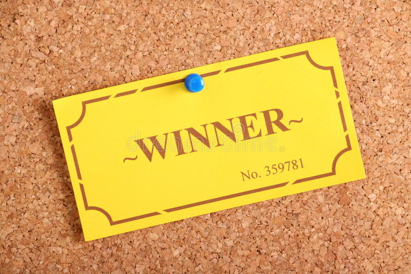 The Winning Ticket. The winning golden raffle or lottery ticket pinned to a cork notice board as a concept for being a winner or achiever royalty free stock images