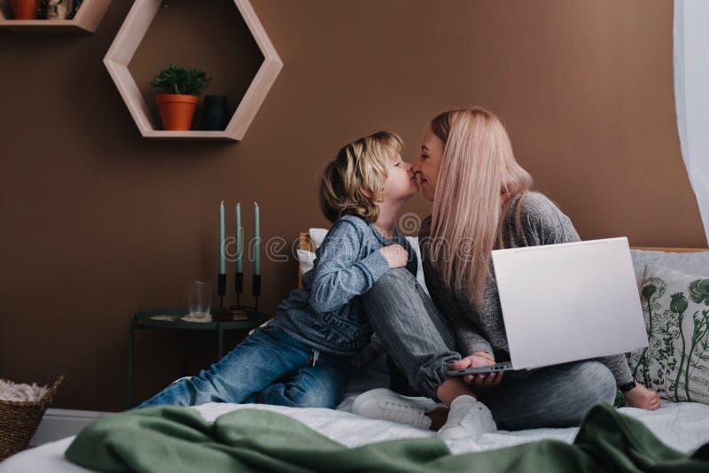 Wiith do freelancer da mulher seu filho que usa o laptop portátil em casa fotos de stock