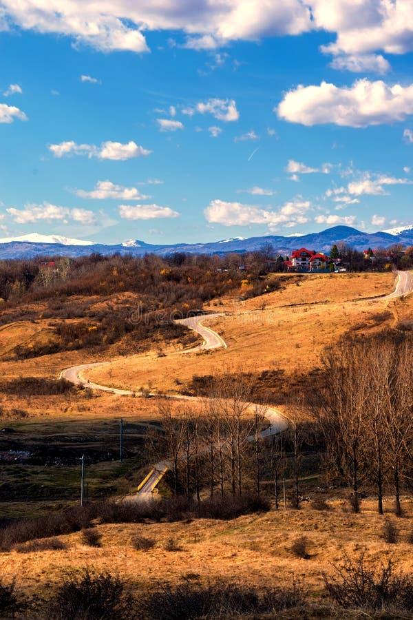 Wijąca droga przez wzgórzy w wczesnym wiosna czasie, śniegu i zakrywał halnych szczyty w dalekim tle obrazy stock