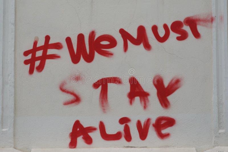 Wij moeten levend, luchtpenseelcitaat op een muur van Boekarest blijven stock foto