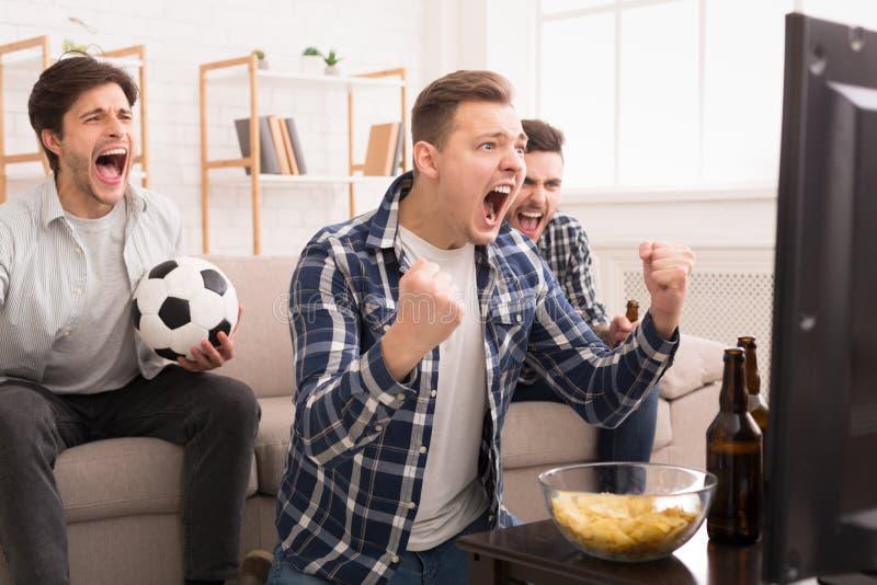 Wij winnen! Emotionele Voetbalventilators die op Gelijke op TV letten stock fotografie