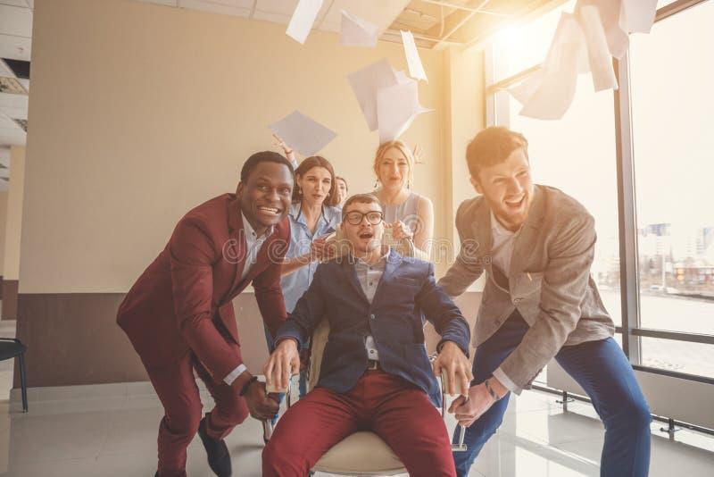 Wij zijn de winnaars bedrijfsmensen die pret hebben terwijl het rennen op bureaustoelen stock afbeelding