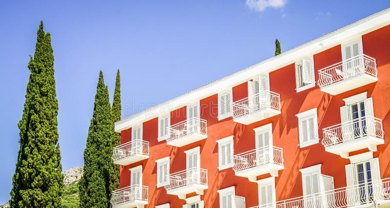 Wijd geschoten van een groot oranje huis met witte vensters en balkons dichtbij lange bomen stock foto