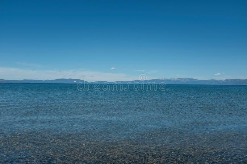 Wijd geschoten van het Meer Tahoe, met bergen en blauwe duidelijke hemel op de achtergrond in Californië de V.S. royalty-vrije stock foto