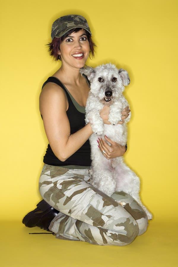 Wijfje dat een kleine hond houdt. stock foto