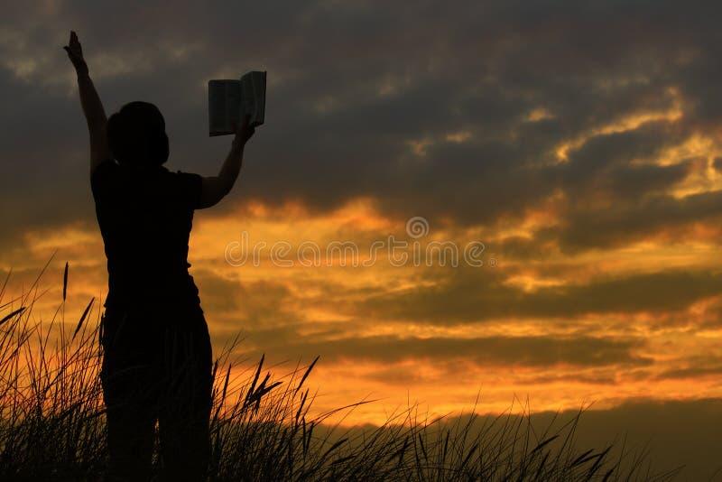 Wijfje dat met bijbel bidt stock afbeelding