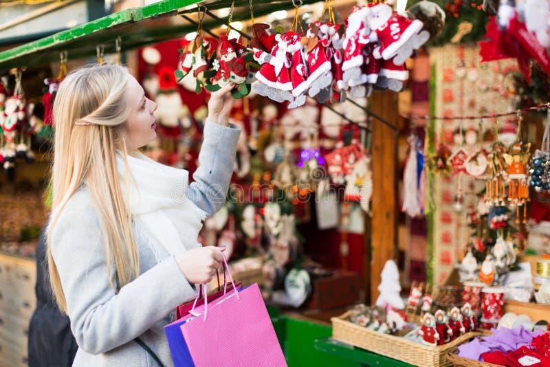Wijfje dichtbij teller met Kerstmisgiften stock afbeeldingen