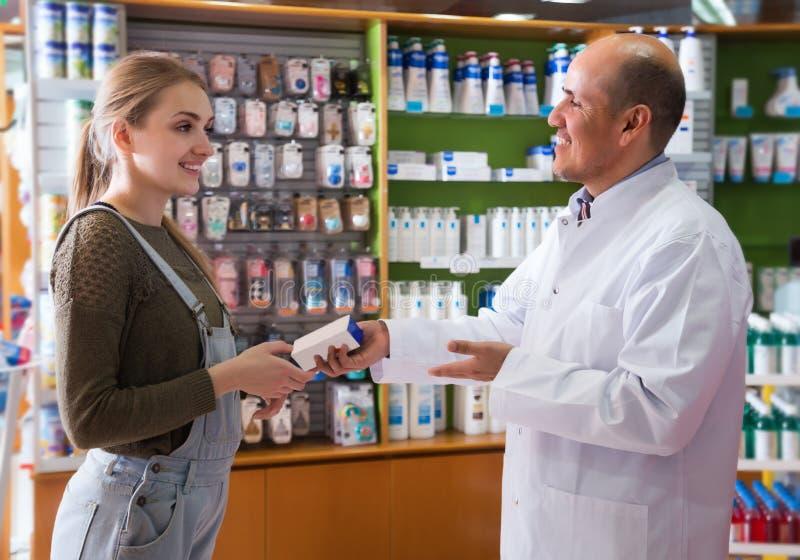 Wijfje die aan een apotheker spreken stock foto's