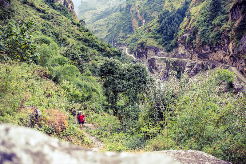 Wijfje die backpacker met rugzak in Himalayagebergte, Nepal beklimmen royalty-vrije stock fotografie