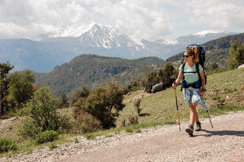 Wijfje die backpacker onderaan de weg in heuvels lopen royalty-vrije stock afbeelding