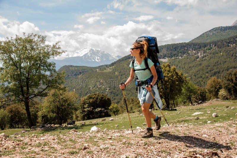 Wijfje die backpacker onderaan de weg in heuvels reizen stock fotografie