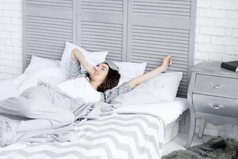 Wijfje die in bed liggen Ochtendkielzog op concept stock afbeeldingen