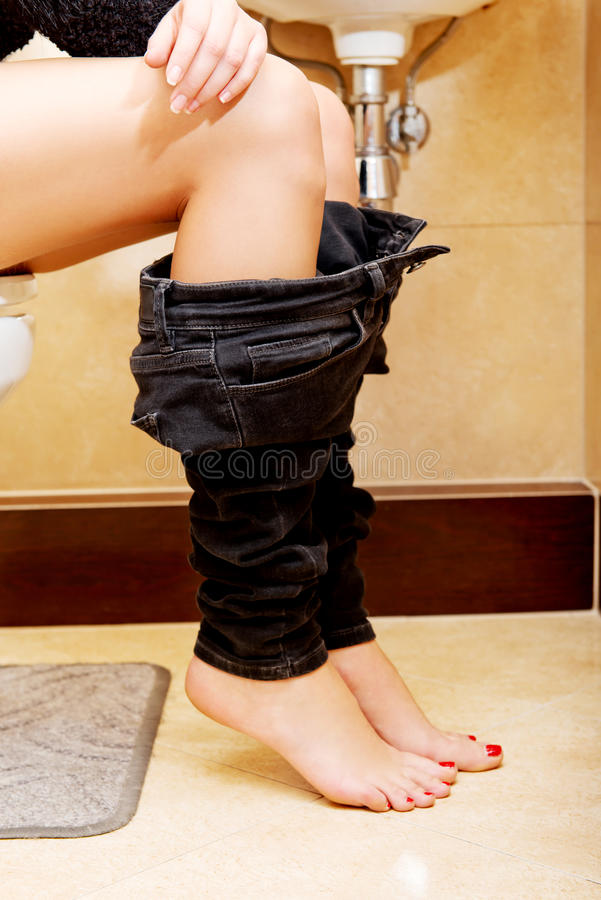 Wijfje die bij een toilet met haar neer broek plaatsen royalty-vrije stock afbeelding