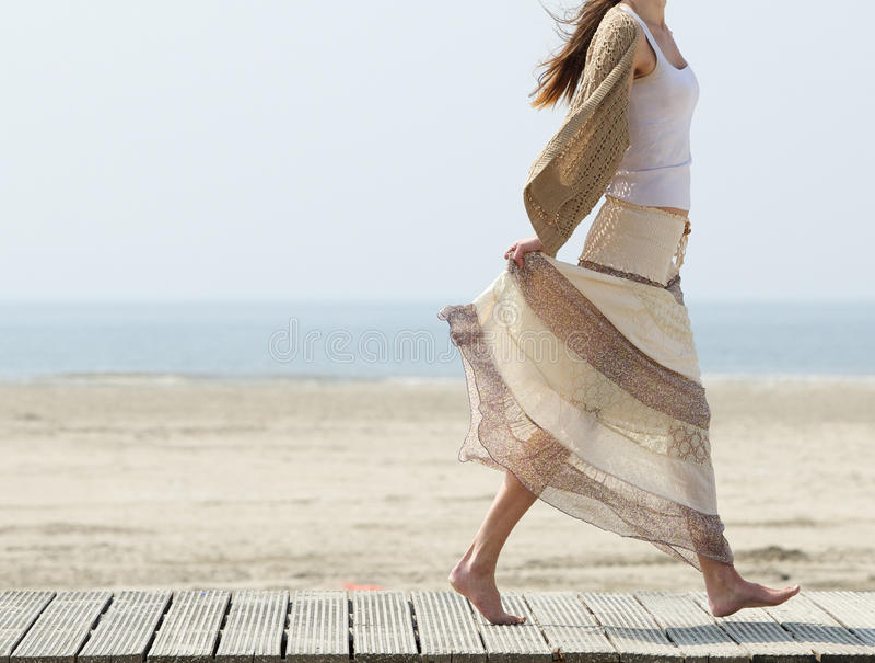 Wijfje die bij het strand blootvoets met kleding lopen stock afbeeldingen