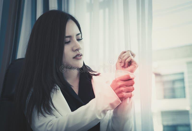 Wijfje die de verwonding van het bureausyndroom op haar pols hebben handwortel royalty-vrije stock fotografie