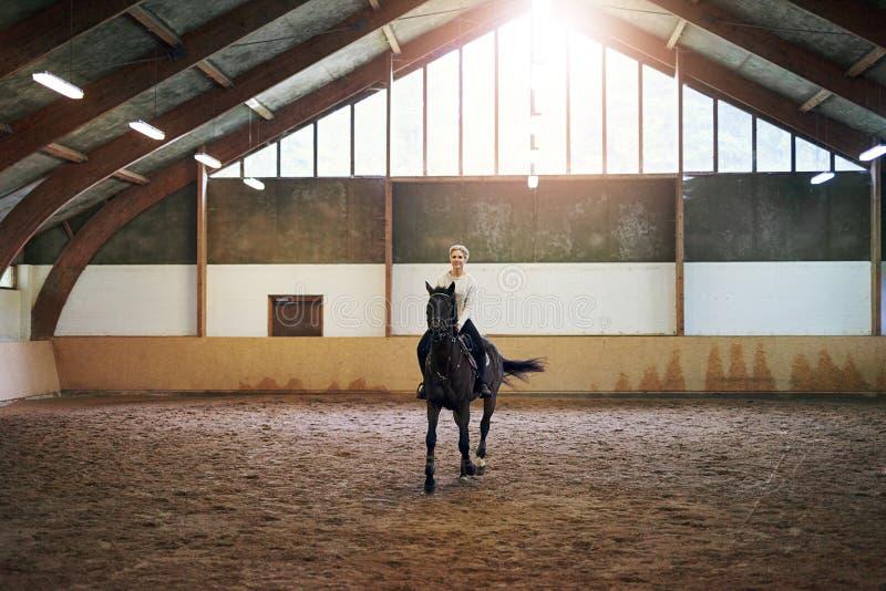 Wijfje die donker paard in binnenpaddock berijden royalty-vrije stock foto