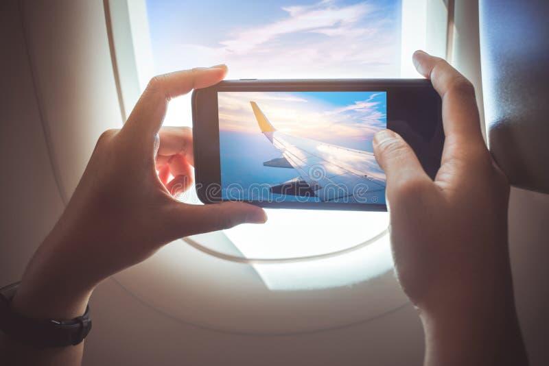 Wijfje die een foto met smartphone op vliegtuig nemen Vakantiereis royalty-vrije stock foto