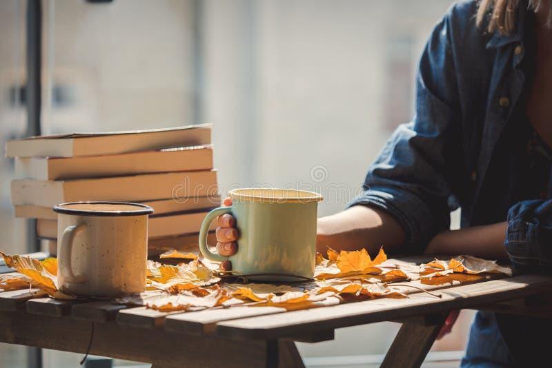 Wijfje die een koffie van kopfo houden met boeken in hand stock fotografie