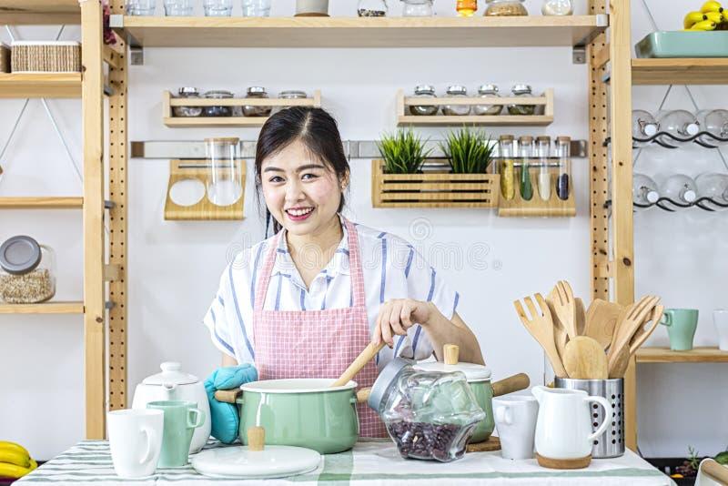 Wijfje die een lepel in de keuken houden Het portret van een mooie lepel van de vrouwenholding maakte gezond voedsel in de keuken stock foto