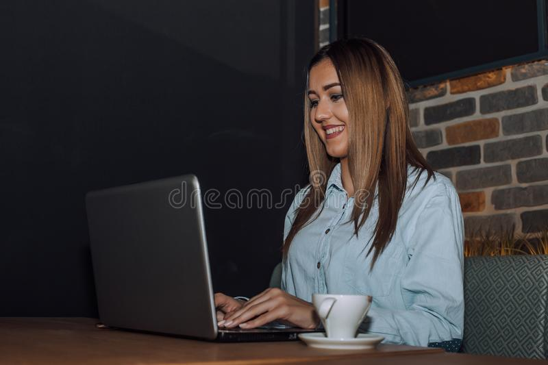 Wijfje die freelancer aan laptop in een koffie werken royalty-vrije stock afbeelding