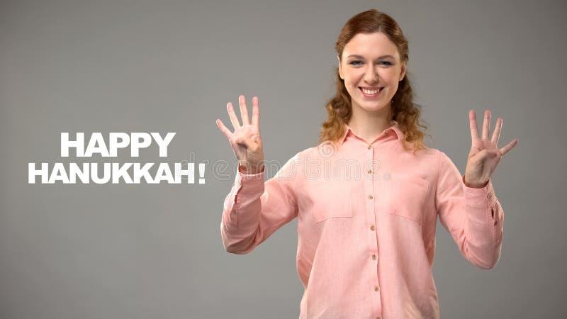 Wijfje die gelukkige hanukkah in gebarentaal, tekst op achtergrond, mededeling zeggen royalty-vrije stock foto's