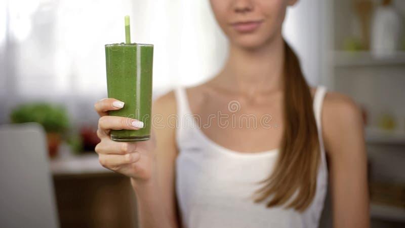 Wijfje die groene gezonde smoothie, vegetarisch groentesap, natuurlijke drank tonen royalty-vrije stock fotografie
