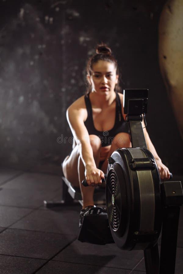 Wijfje die het roeien machine in gymnastiek met behulp van vrouw die cardiotraining in geschiktheidsclub doen stock foto