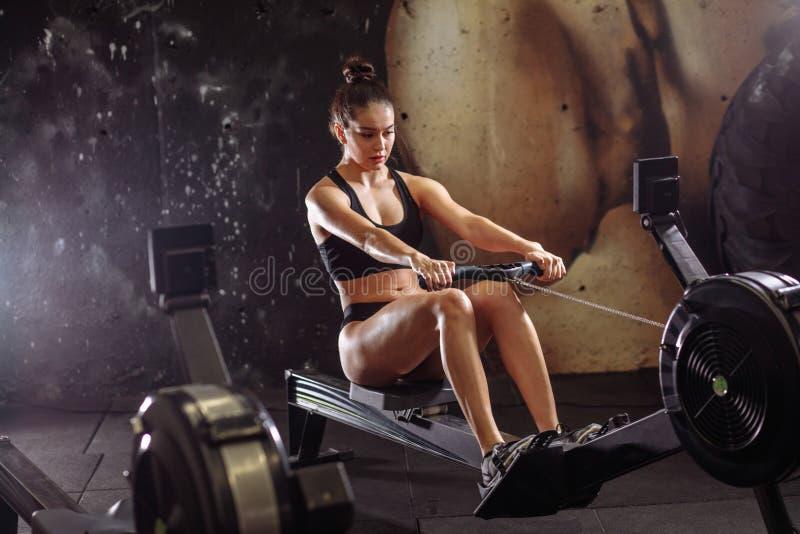 Wijfje die het roeien machine in gymnastiek met behulp van vrouw die cardiotraining in geschiktheidsclub doen stock foto's