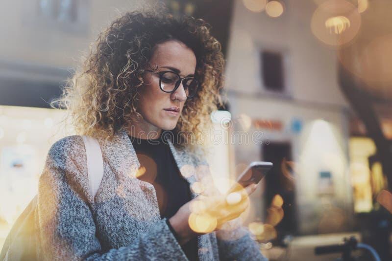 Wijfje die hipster rugzak en glazen dragen die informatie binnen zoeken in mobiel netwerk door slimme telefoon, tijdens gang royalty-vrije stock afbeelding