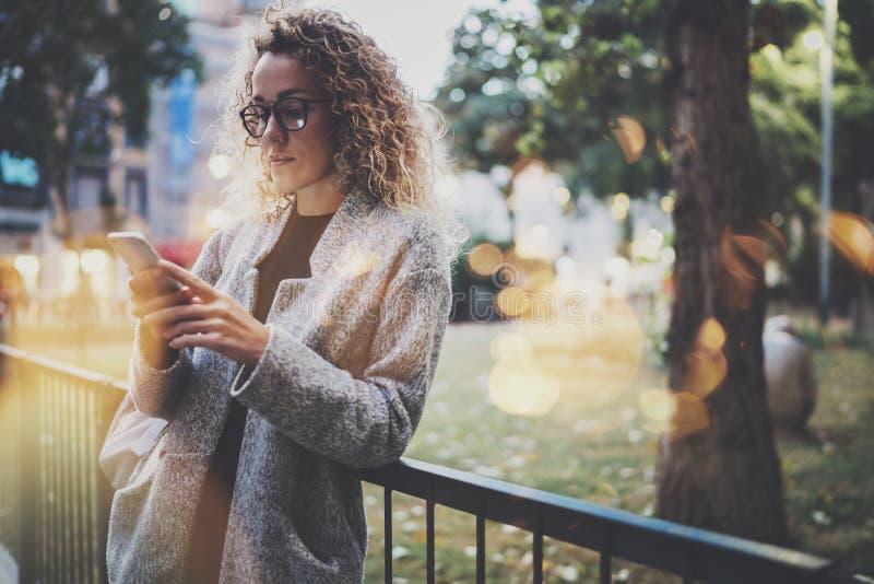 Wijfje die hipster rugzak en glazen dragen die informatie binnen zoeken in mobiel netwerk door slimme telefoon, tijdens gang stock fotografie