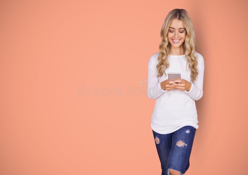 Wijfje die hipster slimme telefoon met behulp van tegen oranje achtergrond royalty-vrije stock foto