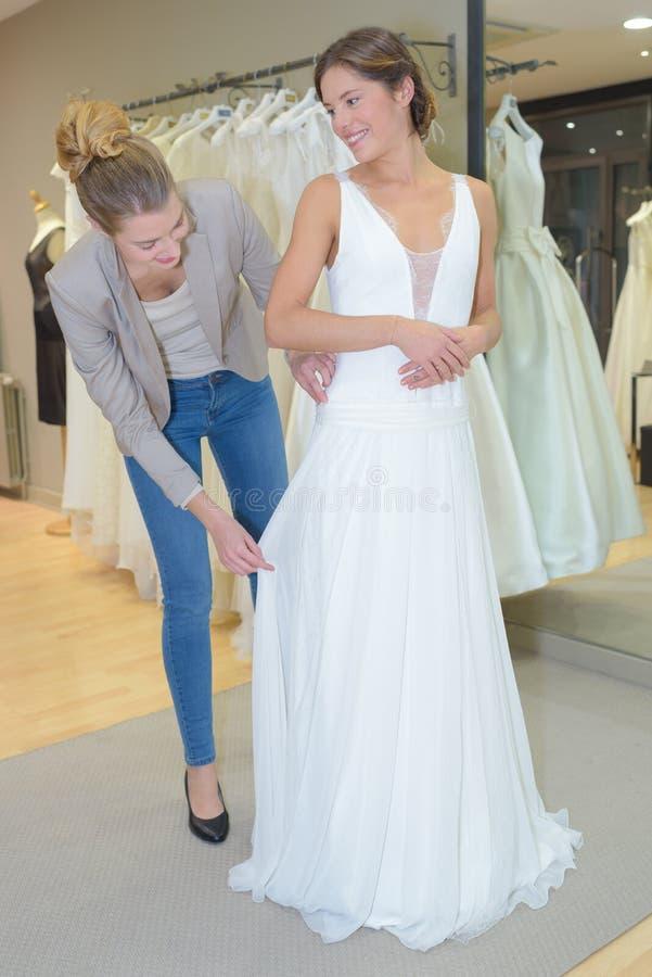 Wijfje die huwelijkskleding in winkel met vrouwenmedewerker proberen royalty-vrije stock foto