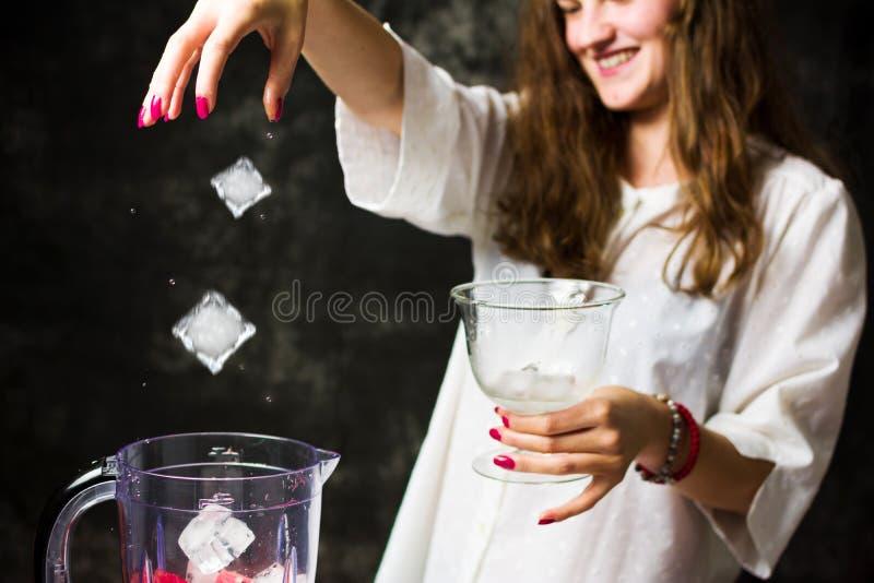 Wijfje die ijs toevoegen in mixer met watermeloen stock afbeelding