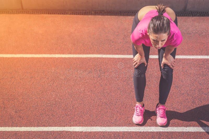 Wijfje die jogger een onderbreking op renbaan nemen royalty-vrije stock afbeeldingen