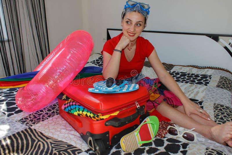 Wijfje die Klaar voor het Reizen worden jonge mooie vrouw, rode koffer, zitting, wachten, de zomervakantie, kleurrijk, reizend AR stock foto's