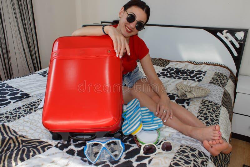 Wijfje die Klaar voor het Reizen worden jonge mooie vrouw, rode koffer, zitting, wachten, de zomervakantie, kleurrijk, reizend AR royalty-vrije stock fotografie