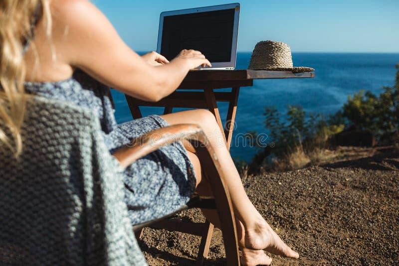 Wijfje die met haar laptop dichtbij het overzees werken stock foto's