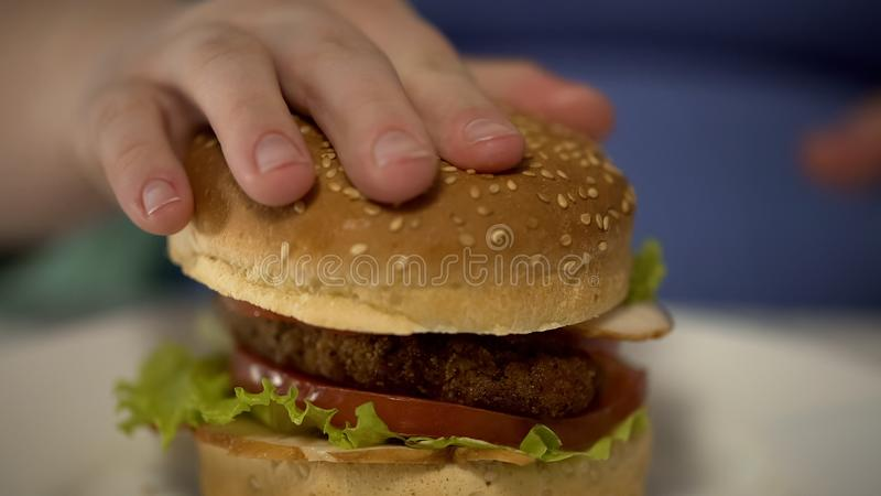 Wijfje die ongezond vettig hamburger, zwaarlijvigheids en het te veel eten probleem voorbereidingen treffen te eten royalty-vrije stock foto