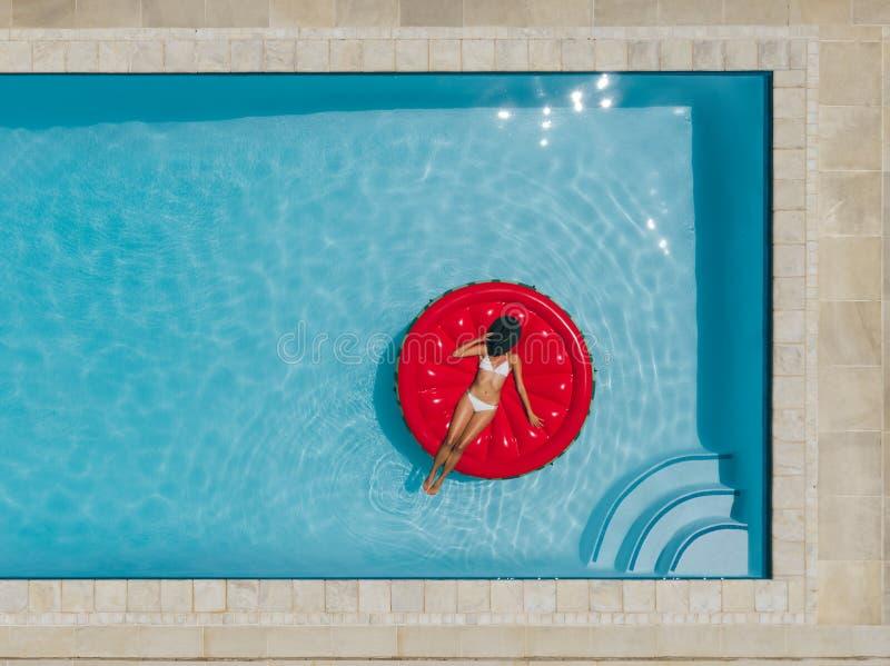 Wijfje die op drijvende matras in pool zonnebaden royalty-vrije stock fotografie