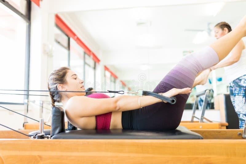 Wijfje die op Pilates-Hervormer in Gezondheidsclub uitoefenen royalty-vrije stock afbeeldingen