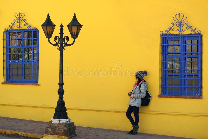 Wijfje die tegen levendige gele ruwe muur met levendige blauwe artistieke vensters en een uitstekende schitterende straatlantaarn stock fotografie