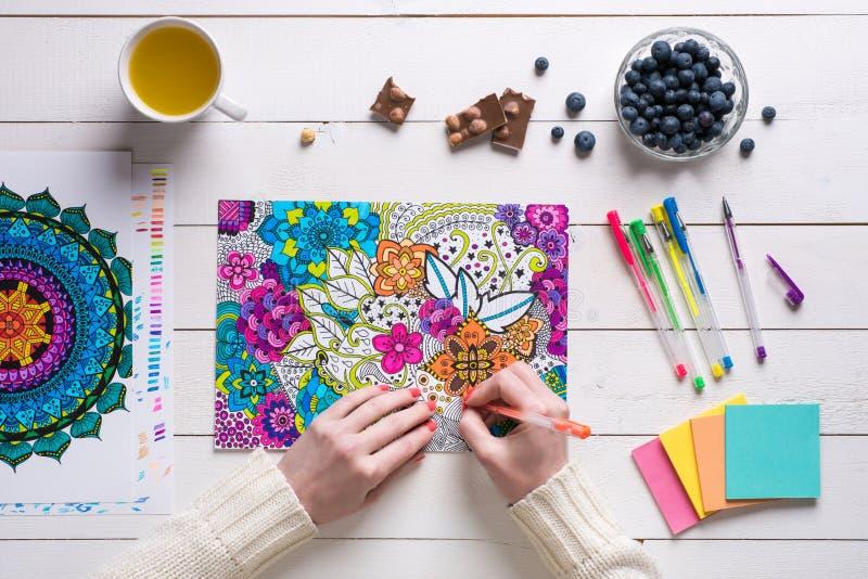 Wijfje die volwassen kleurend boek, mindfulnessconcept kleuren royalty-vrije stock fotografie