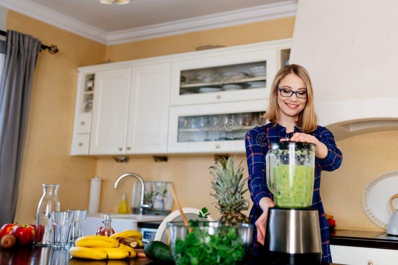 Wijfje die vruchten en groenten in eletrical mixer mengen royalty-vrije stock foto